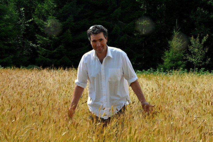 Petter Simonsen er glad i å kjenne på kornet. Han berømmer det biodynamiske miljøet for planteforedlingsarbeidet. Foto: Ragna Kronstad